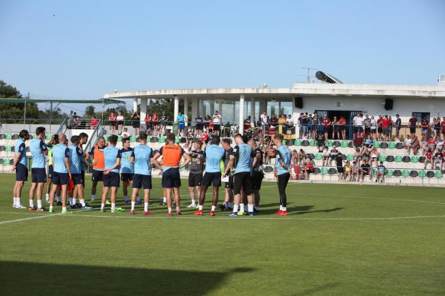 Bryan Hughes speaks with his players during the Portugal training camp