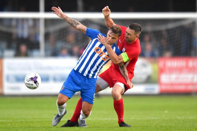Kilmarnock's Eamonn Brophy is tackled by Connor Quay's George Horan during the Europa League, Qualifying First Round match at Belle Vue Stadium, Rhyl.