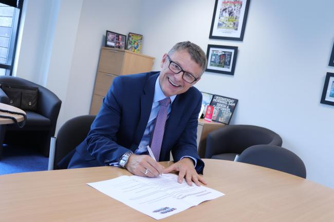 Gary Doherty, Chief Executive, signs the Health Board's commitment to the Let's Get Moving campaign.