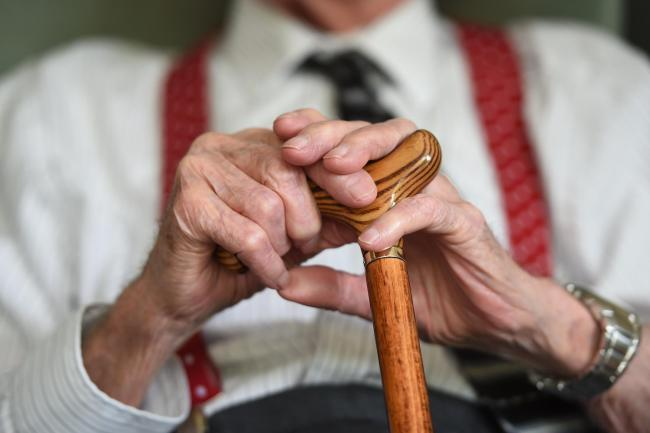 An old man's hands resting on a walking stick