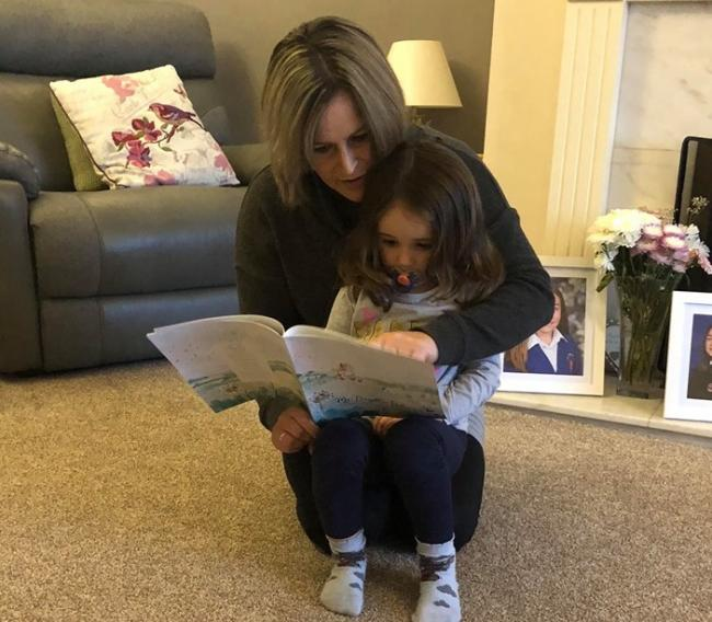 Nevmah Morris reads her book to her daughter Phoebe for the first time.