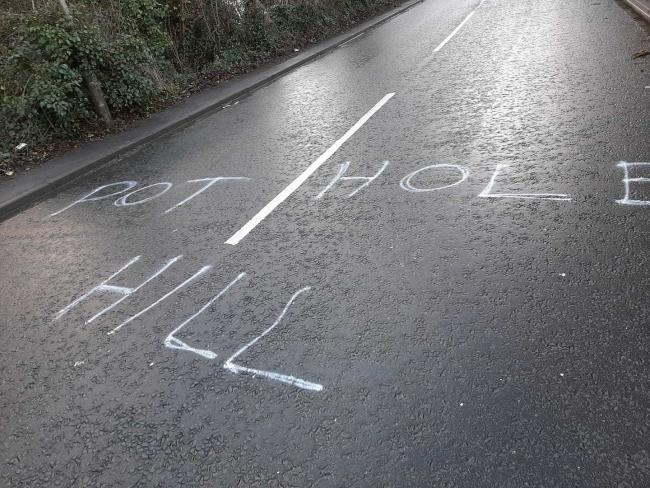 An angry motorist scrawled 'Pothole Hill' on the A5026 (Boot Hill) in Bagillt.