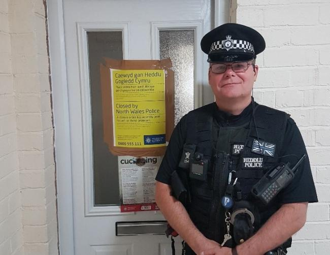 NPT Officer Graham Bailey assisting colleagues in Caia issuing another 24 Hour Closure Notice on a flat in Caia Park.