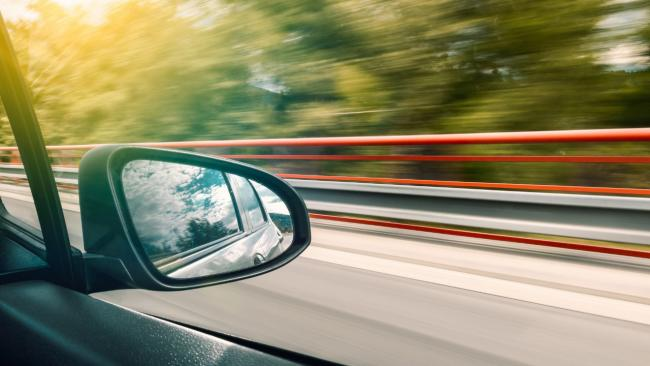 Stock image of a car driving along a road