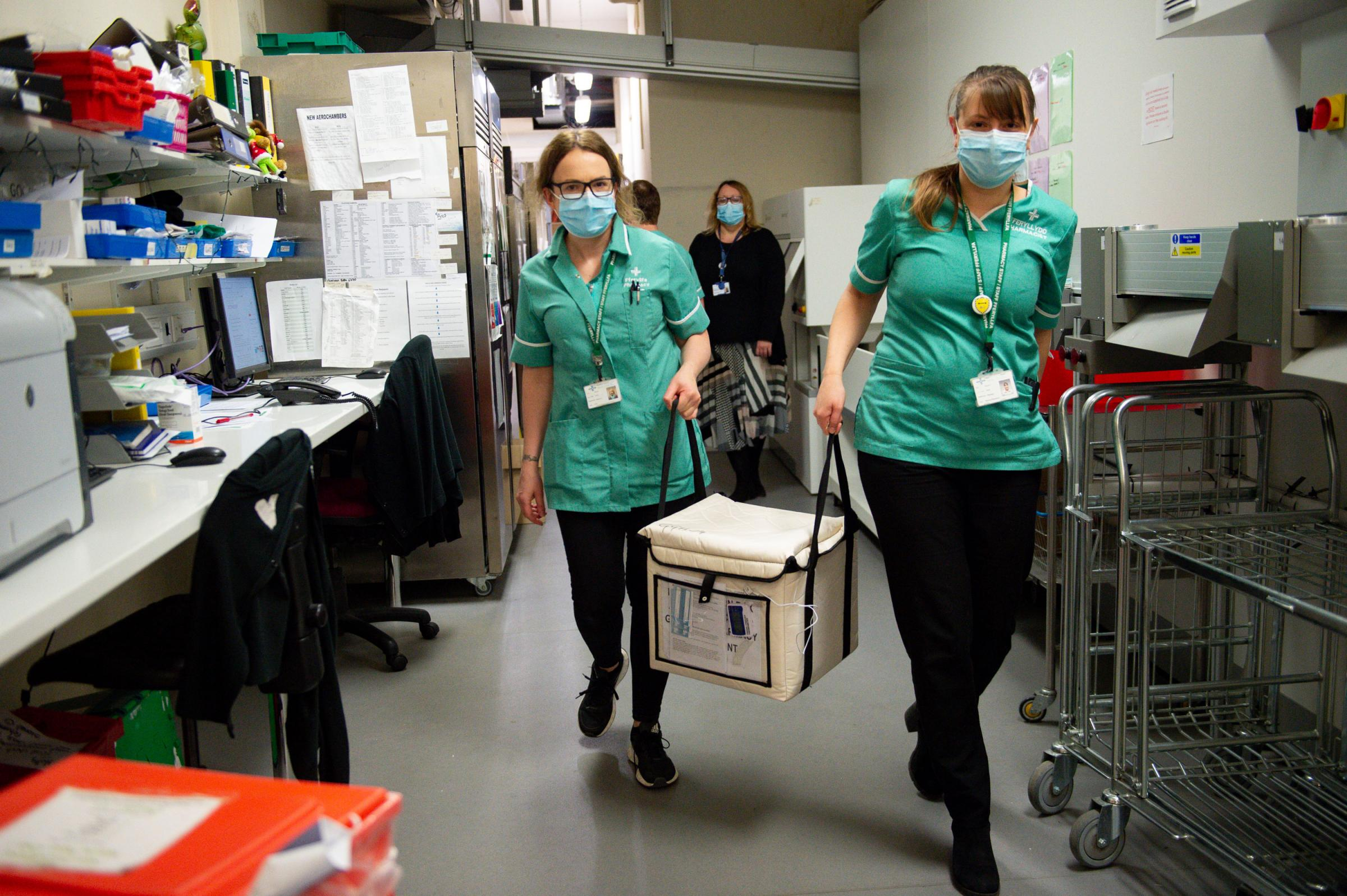 Pharmacists transport a cooler containing the Moderna vaccine, at the West Wales General Hospital in Carmarthen, the third vaccine to be approved for use in the UK, which is to be given to patients in Wales from Wednesday. Picture date: Wednesday April