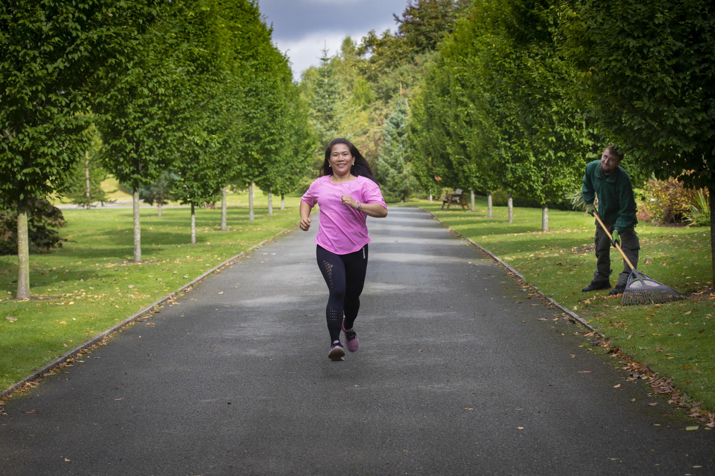 Pendine Park, bodlondeb nursing practitioner Evelyn Dimatu, who raises funds through a charity run for Nova Martin-Roxburgh, three, and practices on the grounds of Pendine Park, is Evelyn Dimatu, who is watched by gardener Jamie Roberts.  Photo: Mandy Jones