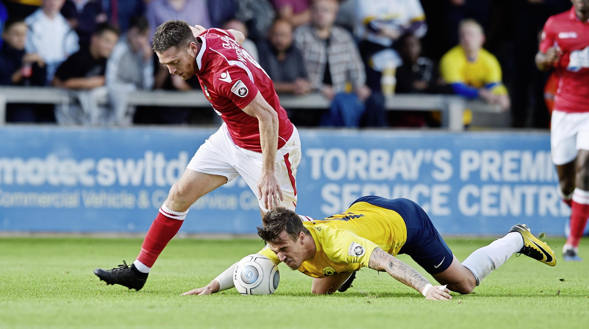 Sam Wedgbury of Wrexham brings down James Gray of Torquay United,   during the Vanarama National League match between Torquay United and Wrexham at Plainmoor, Torquay, Devon on September 09 - PHOTO: Sean Hernon/PPAUK