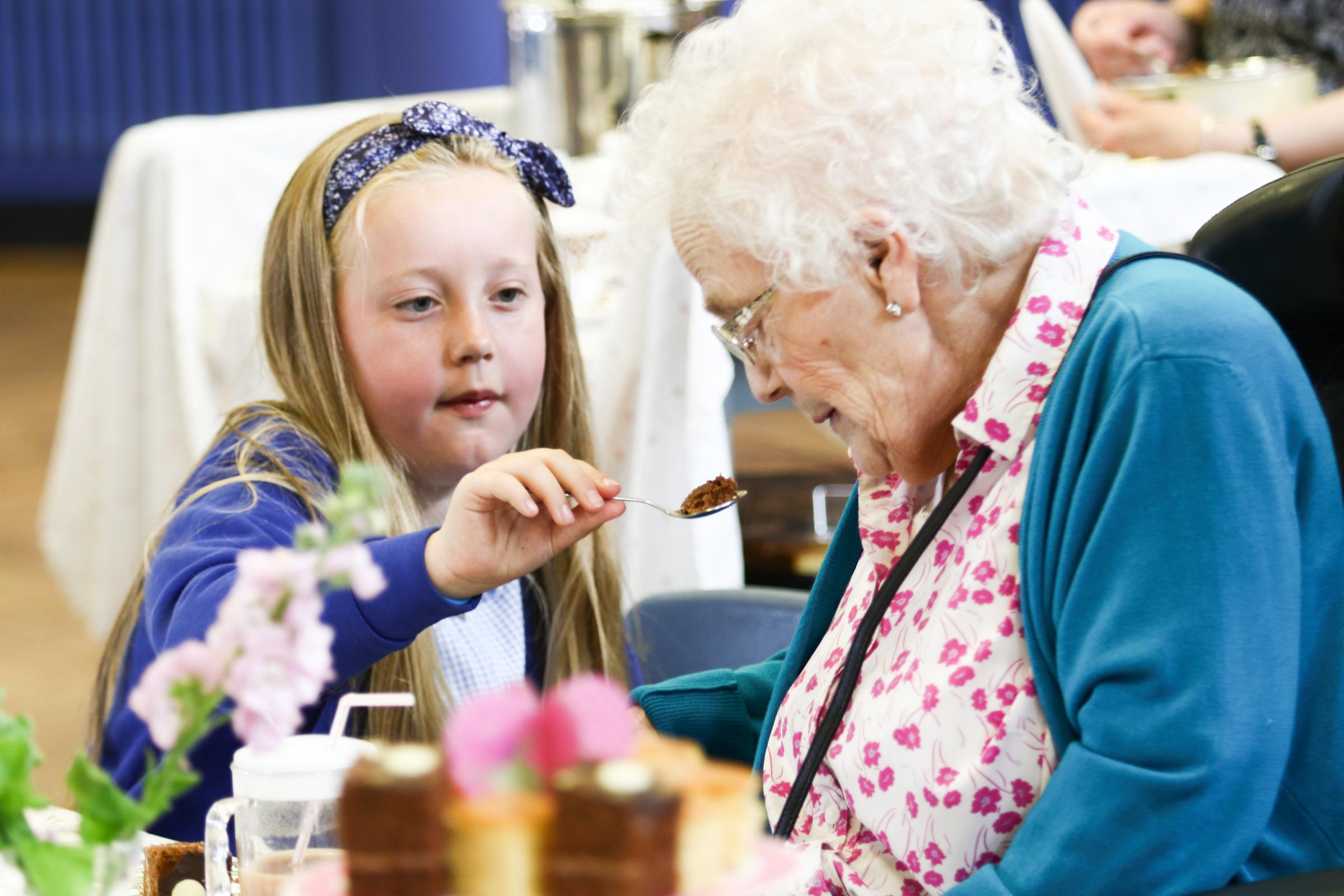 Elderly residents from the Cottage Nursing Home enjoy a Royal Tea and entertainment at Ysgol Bryn Coch. Pic: Harriet Floyd, 9, helps Gwen Griffith with her cake. GA150518D.