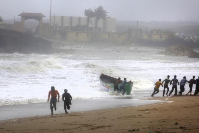 People try to pull back a fishing boat that was carried away by waves on the Arabian Sea coast in Veraval, Gujarat, India